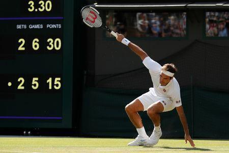 Tennis - Wimbledon - All England Lawn Tennis and Croquet Club, London, Britain - July 11, 2018. Switzerland's Roger Federer slips during his quarter final match against South Africa's Kevin Anderson. REUTERS/Andrew Boyers