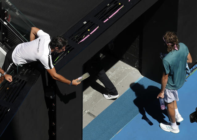 Patrick Mouratoglou looks to pass a drink to Greece's Stefanos Tsitsipas as he leaves the court for a break after the third set in his quarterfinal match against Spain's Roberto Bautista Agut at the Australian Open tennis championships in Melbourne, Australia, Tuesday, Jan. 22, 2019. (AP Photo/Kin Cheung)