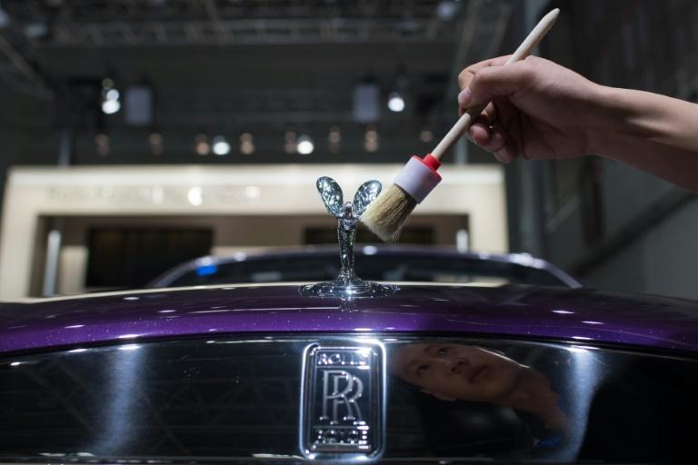 A worker cleans a Rolls Royce car on the eve of the Beijing Auto Show