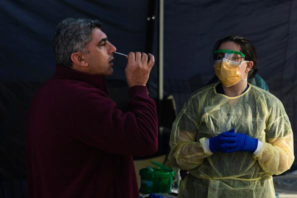 A man places as swab in his nose as he is tested at a pop-up testing facility, during a COVID-19 testing blitz in the suburb of Broadmeadows in Melbourne, Australia.