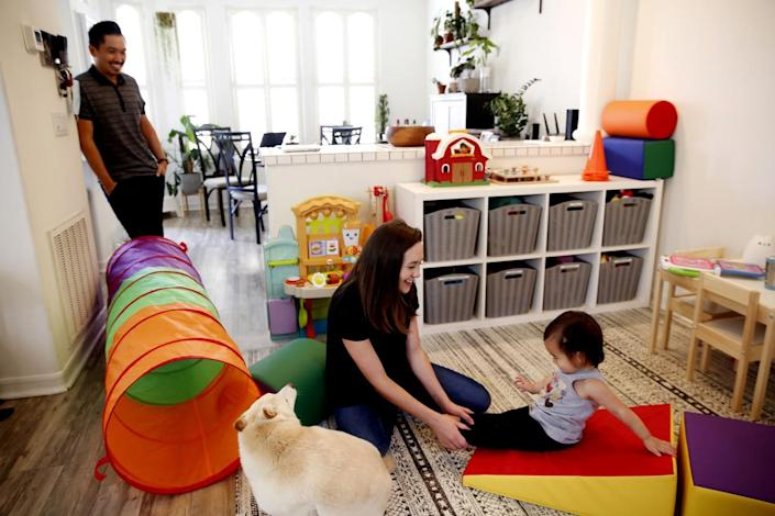 A couple get down on the floor to play with their baby daughter, center.