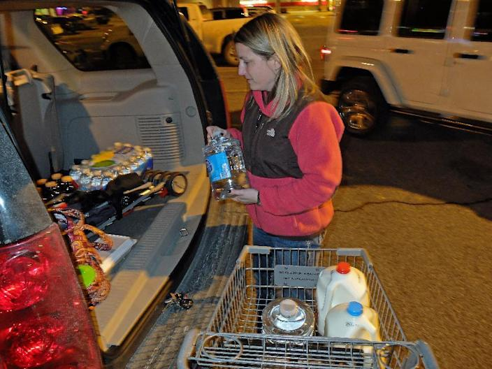 Laura John of Charleston, W.Va, drove across town to South Charleston, W.Va, to find water following a chemical spill on the Elk River that compromised the public water supply of eight counties of Thursday, Jan. 9, 2014. (AP Photo/Tyler Evert)