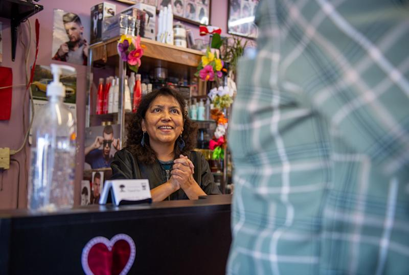Fausta Ibarra, 59, owner of Tropical Cuts Beauty Salon in Salinas greets a costumer early morning on Feb. 07, 2020.