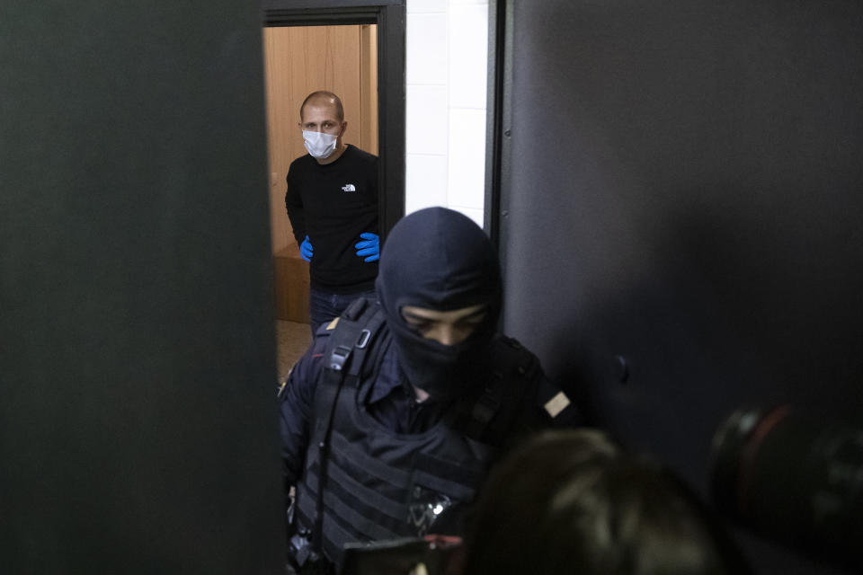 A police officer and an investigator stands behind the door of the apartment of jailed opposition leader Alexei Navalny in Moscow, Russia, Wednesday, Jan. 27, 2021. Police are searching the Moscow apartment of jailed Russian opposition leader Alexei Navalny, another apartment where his wife is living and two offices of his anti-corruption organization. Navalny's aides reported the Wednesday raids on social media. (AP Photo/Pavel Golovkin)
