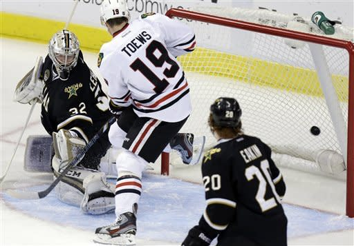 Chicago Blackhawks center Jonathan Toews (19) scores a goal against Dallas Stars goalie Kari Lehtonen (32) as Cody Eakin (20) watches during the first period of an NHL hockey game, Saturday, March 16, 2013, in Dallas. (AP Photo/LM Otero)