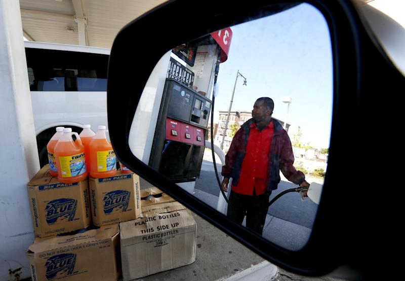 FILE-In this Wednesday, Sept. 12, 2012, file photo, gas station attendant Youssouf Soukouna, 42, pumps gas into a vehicle at a LukOil station where all levels of gas were priced at $4.99, in Newark, N.J.  Higher gas prices are crimping consumer spending and slowing the already-weak U.S. economy. And they could get worse in the coming months. The Federal Reserve this week took steps to boost economic growth. But those stimulus measures are also pushing oil prices up. If gas prices follow, consumers will have less money to spend elsewhere. (AP Photo/Julio Cortez, File)