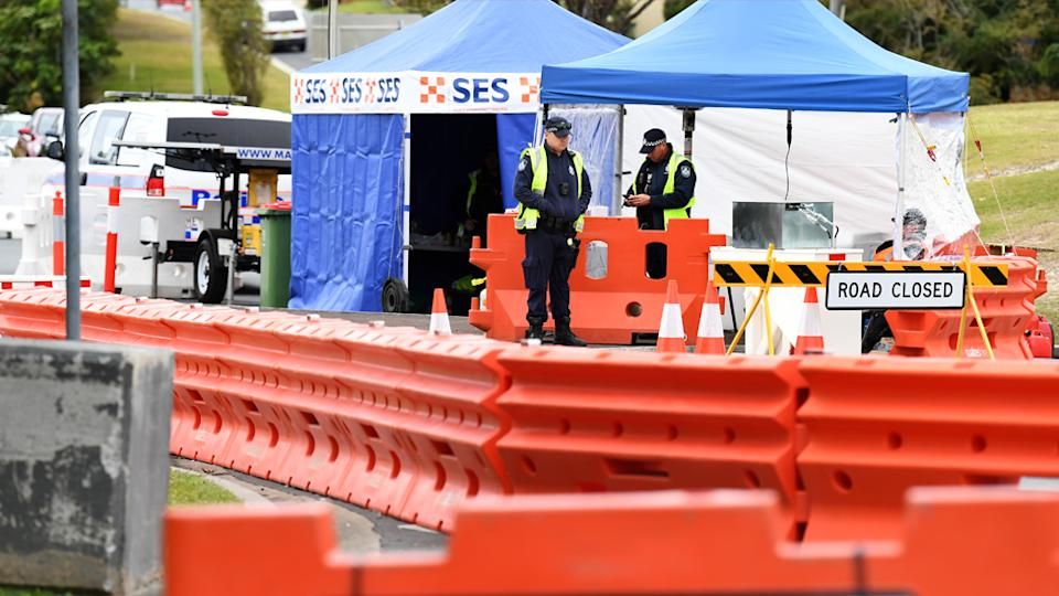 Police officers are seen at a checkpoint on the Queensland-New South Wales border in Coolangatta on the Gold Coast, Thursday, July 23, 2020