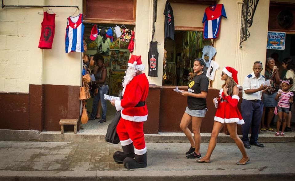 People wearing Santa Claus costumes give out leaflets promoting a restaurant in the streets of Havana, Cuba, on December 23, 2014 (AFP Photo/Yamil Lage)
