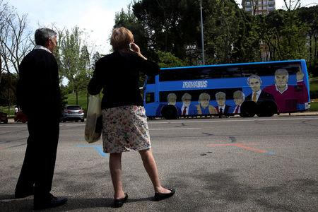 People look at a bus sponsored by Podemos (We can) party painted with pictures representing Spain's recent political scandals as it tours Madrid, Spain April 18, 2017. Picture taken April 18, 2017. REUTERS/Susana Vera