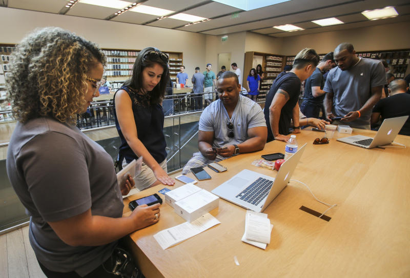 An Apple employee processes a transaction as customers purchase Apple's iPhone 6s and iPhone 6s Plus smartphones Friday, Sept. 25, 2015 at the Apple store at The Grove in Los Angeles. Apple is counting on sales of the new iPhones to maintain its position as one of the most profitable, and valuable, companies in the world. (AP Photo/Ringo H.W. Chiu)