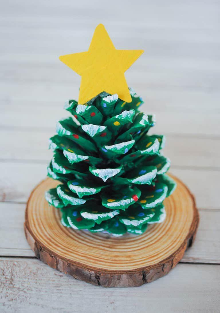 """<p>Use pinecones, wood slices, and acrylic paint to create this Christmas tree project, perfect for displaying as a table centerpiece or clustered on the mantle. Try it with foraged objects if you can — but buying them works, too!</p><p><em><a href=""""https://pjsandpaint.com/crafts/pinecone-christmas-tree-craft/"""" rel=""""nofollow noopener"""" target=""""_blank"""" data-ylk=""""slk:Get the tutorial at PJs and Paint"""" class=""""link rapid-noclick-resp"""">Get the tutorial at PJs and Paint</a></em></p>"""
