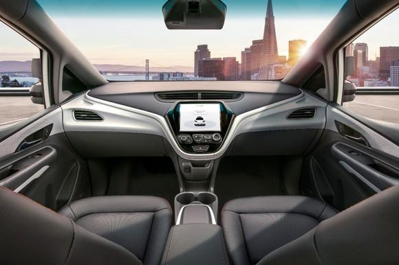 A view of the front seat and dash of the Cruise AV. The vehicle has no steering wheel and no pedals.