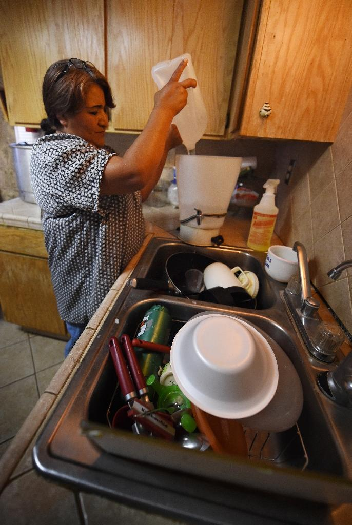 Maria Jimenez demonstrates how they use bottled water to wash dishes in the drought affected town of Monson, California on June 23, 2015 (AFP Photo/Mark Ralston)