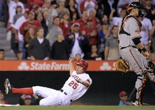 Los Angeles Angels' Peter Bourjos, left, is safe at home as he alides by Baltimore Orioles catcher Matt Wieters on a single by Bobby Abreu during the fith inning of their baseball game, Saturday, April 21, 2012, in Anaheim, Calif. (AP Photo/Mark J. Terrill)