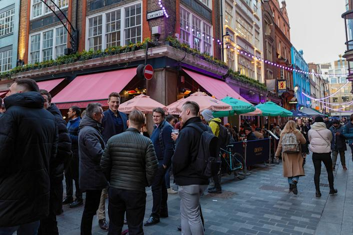LONDON, UNITED KINGDOM - 2021/04/15: People enjoying food and drinks in Carnaby Street area. As the lockdown restrictions are eased from 12th April, people are able to eat and drink outside London's pubs, bars, restaurants and cafes. The