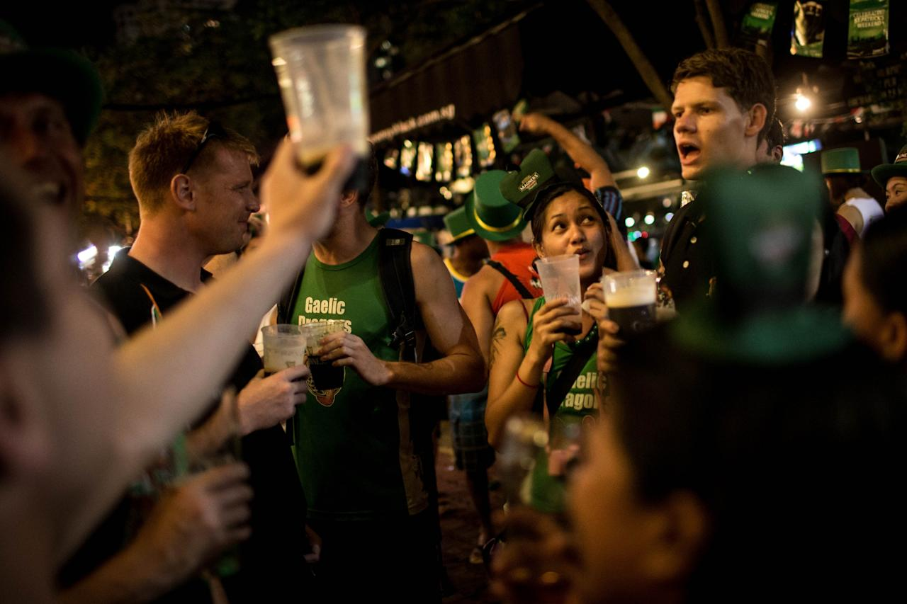 SINGAPORE - MARCH 17:  People drink beer to celebrate St Patricks Day during the Singapore St Patrick's Day street Festival at Boat Quay on March 17, 2013 in Singapore.  Singapore's Irish community gathered at Boat Quay for a three-day-long St Patrick's Day Street Festival which featured street performances, buskers, and Irish food and drink.  (Photo by Chris McGrath/Getty Images)