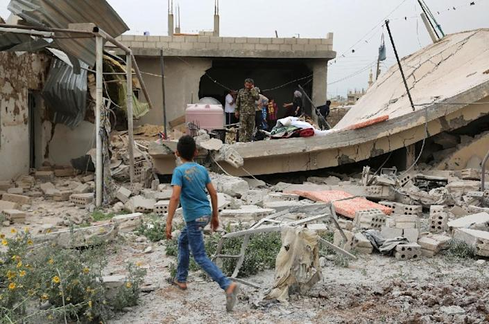 Syrians inspect the damage following clashes between Syrian pro-government fighters and Kurdish forces, in the northeastern city of Qamishli, on April 21, 2016 (AFP Photo/Delil Souleiman)