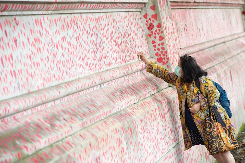 A woman writes a message on the Covid memorial wall in Westminster, London (Dominic Lipinski/PA) (PA Wire)