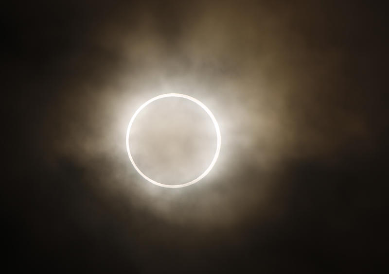 An annular eclipse appears at a waterfront park in Yokohama, near Tokyo, Monday, May 21, 2012. The annular eclipse, in which the moon passes in front of the sun leaving only a golden ring around its edges, was visible to wide areas across China, Japan and elsewhere in the region before moving across the Pacific to be seen in parts of the western United States. (AP Photo/Shuji Kajiyama)