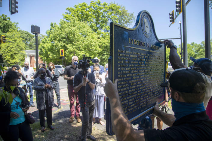 People gather to watch the installation of a historical marker that tells the story of the lynching of Porter Flournoy Turner in Atlanta's Druid Hills community, Thursday, May 6, 2021. Porter Turner was lynched near the area in August 1945. (Alyssa Pointer/Atlanta Journal-Constitution via AP)