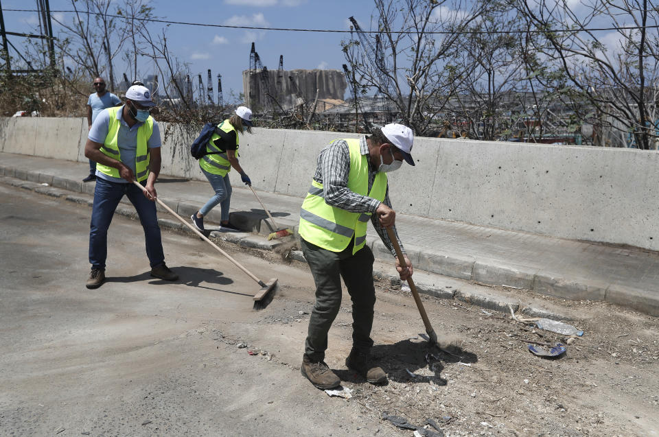 Volunteers who traveled from the Bekaa valley in Eastern Lebanon to help clean the city, damaged homes and give other assistance, clean a street near the site of last week's explosion, in Beirut, Lebanon, Tuesday, Aug. 11, 2020. The explosion that tore through Beirut left around a quarter of a million people with homes unfit to live in. In the absence of the state residents of Beirut opened their homes to relatives, friends and neighbors. And on the streets, it was young volunteers with brooms, not government workers, who swept the streets littered with shattered glass. (AP Photo/Hussein Malla)
