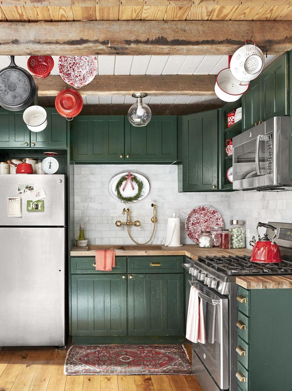 """<p>It never hurts to take color cues from the great outdoors—especially when you've got views of rolling hills, pretty pastures, and trees galore. In this small kitchen, cabinets in <a href=""""https://www.sherwin-williams.com/homeowners/color/find-and-explore-colors/paint-colors-by-family/SW6216-jasper"""" rel=""""nofollow noopener"""" target=""""_blank"""" data-ylk=""""slk:Jasper by Sherwin-Williams"""" class=""""link rapid-noclick-resp"""">Jasper by Sherwin-Williams</a> positively pop against white tile, exposed beams, and beautiful wood floors. <br></p>"""
