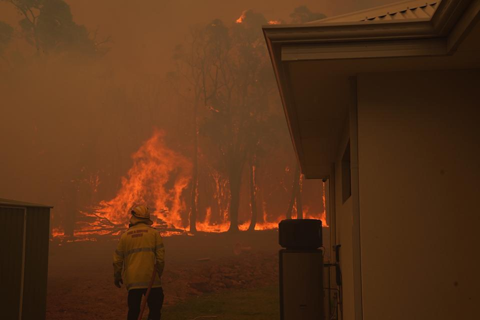A firefighter standing next to a house. Fire burns in the background.