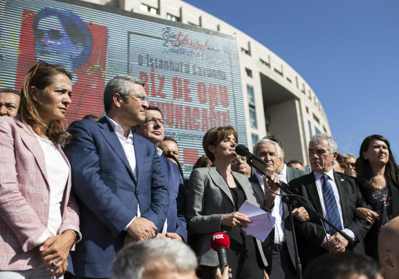 Canan Kaftancioglu, the head of Turkey's secular Republican People's Party in Istanbul, speaks to supporters gathered outside the courthouse after her trial in Istanbul, Friday, Sept. 6, 2019. Turkey's state-run news agency says a court has sentenced the leader of the Istanbul branch of Turkey's main opposition party to nearly 10 years in prison over a series of tweets.(AP Photo)