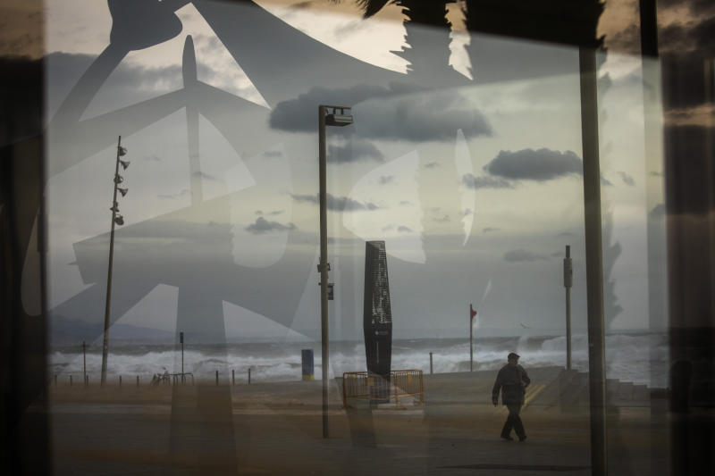A man is seen through a window as he walks near the beach during strong winds in Barcelona, Spain, Monday, Jan. 20, 2020. Two people have died as storms carrying heavy snowfalls and gale-force winds lashed many parts of Spain on Monday. The storm has forced the closure of Alicante airport and some 30 roads in eastern region. Six provinces are on top alert. (AP Photo/Emilio Morenatti)