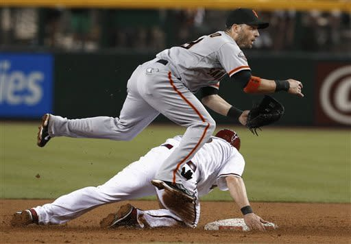 San Francisco Giants' Marco Scutaro, top, jumps over Arizona Diamondbacks' Willie Bloomquist after forcing him out at second base during the first inning in a baseball game on Friday, June 7, 2013, in Phoenix. Paul Goldschmidt was out at first. (AP Photo/Ross D. Franklin)