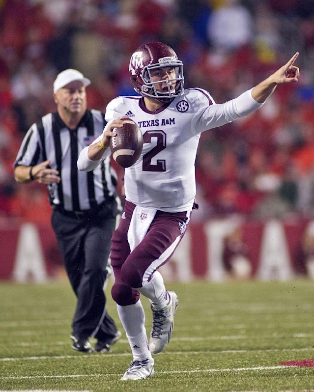 FILE - In this Sept. 28, 2013, file photo, Texas A&M quarterback Johnny Manziel points as he looks to make a pass during an NCAA college football game against Arkansas in Fayetteville, Ark. Manziel has put up eye-popping numbers similar to and in some cases better than he did a year ago, but most polls don't have him favored to join Archie Griffin as the second two-time Heisman winner. (AP Photo/Beth Hall, File)