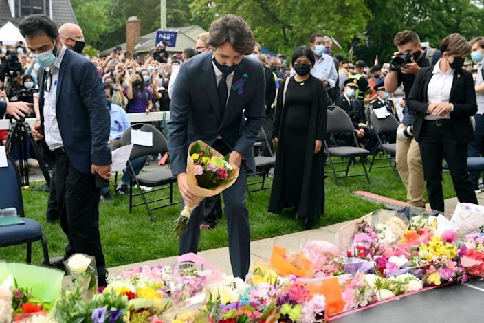 <p>Canada's Prime Minister Justin Trudeau places flowers at a vigil for the victims of the deadly vehicle attack on five members of the Canadian Muslim community in London, Ontario, on Tuesday, June 8, 2021.</p> (Nathan Denette/The Canadian Press via AP)