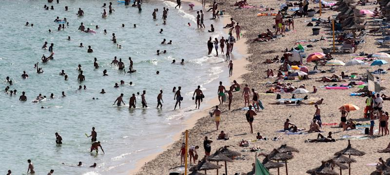 Tourists sunbathe and swim at the beach of Magaluf on the island of Mallorca, Spain, August 18, 2017. Picture taken August 18, 2017. REUTERS/Enrique Calvo