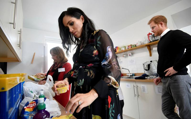 Prince Harry, behind, looks on as Meghan, Duchess of Sussex helps prepare food parcels during her visit to the One25 charity kitchen in Bristol - Pool reuters