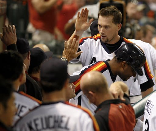 Houston Astros' Chris Johnson is congratulated after hitting a triple on a fly ball against the Pittsburgh Pirates in the seventh inning of a baseball game, Friday, July 27, 2012, in Houston. (AP Photo/Eric Kayne)