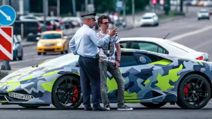 Yakubets speaking with a police officer next to his Lamborghini Huracan.