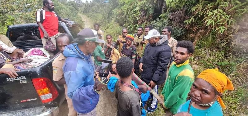 Bagau is carried by his two brothers, among others, on his way to the local health clinic in Intan Jaya regency, Papua
