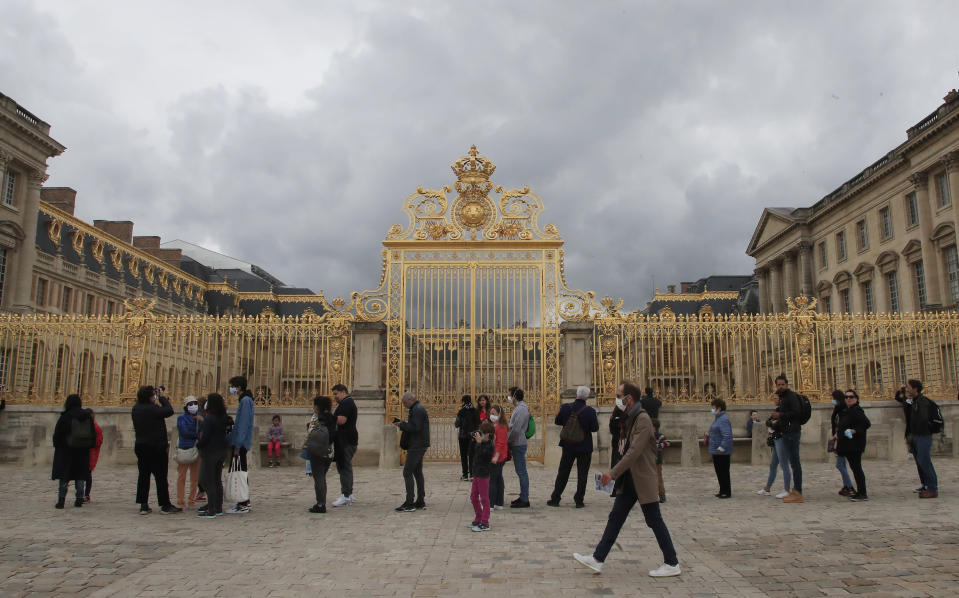 People lining up along the Gate of Honor to visit the Chateau de Versailles, west Paris, Sunday, June 7, 2020. The Chateau de Versailles was reopened on June 6, after Covid-19 closure. (AP Photo/Michel Euler)