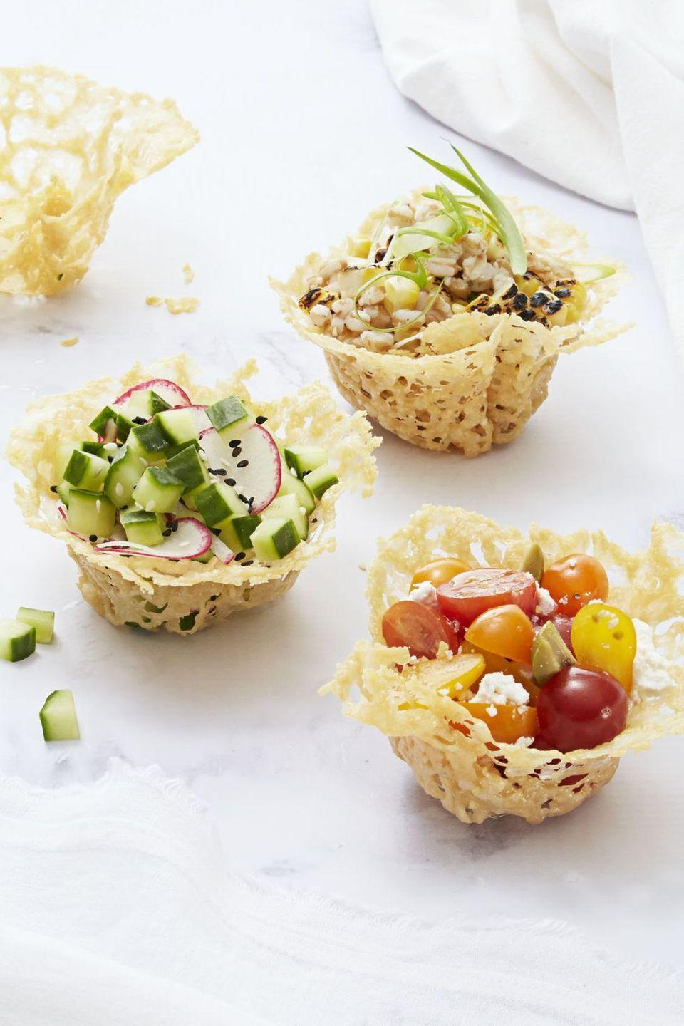 """<p>This delicate, baked Parmesan cheese cups are deceptively easy to make. You can fill them with whatever you want, but grape tomato, olive and feta make for a light and refreshing snack.</p><p><em><a href=""""https://www.goodhousekeeping.com/food-recipes/easy/a34370/frico-cups/"""" rel=""""nofollow noopener"""" target=""""_blank"""" data-ylk=""""slk:Get the recipe for Frico Cups »"""" class=""""link rapid-noclick-resp"""">Get the recipe for Frico Cups »</a></em> </p>"""