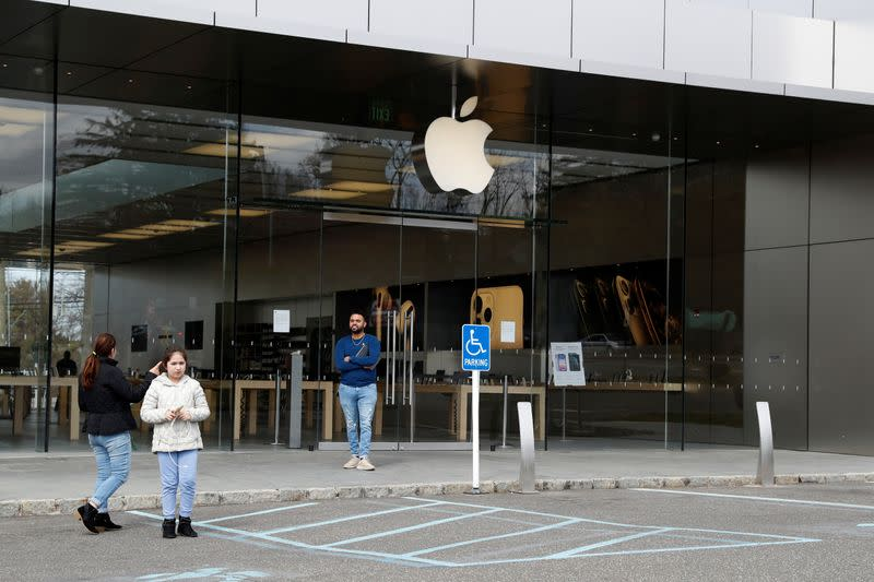 FILE PHOTO:  An Apple store employee informs people that the store is closed, after further cases of coronavirus were confirmed in New York, in Manhasset, New York