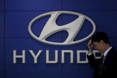 FILE PHOTO: A car dealer stands in front of the logo of Hyundai Motor at its dealership in Seoul