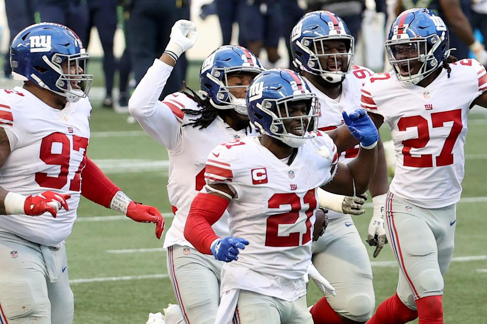 Dexter Lawrence, Jabrill Peppers and Isaac Yiadom of the New York Giants celebrate an interception by Darnay Holmes #30 (not pictured) against the Seattle Seahawks during the fourth quarter in the game at Lumen Field on December 06, 2020 in Seattle, Washington.
