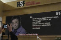 A reporter takes a picture of a board with a portrait of Maria Ressa of the Philippines after the announcement of the Nobel Peace Prize, in the headquarters of Reporters without Borders, known by its French acronym RSF, in Paris, Friday, Oct. 8, 2021. The Nobel Peace Prize has been awarded to journalists Ressa of the Philippines and Dmitry Muratov of Russia. (AP Photo/Francois Mori)