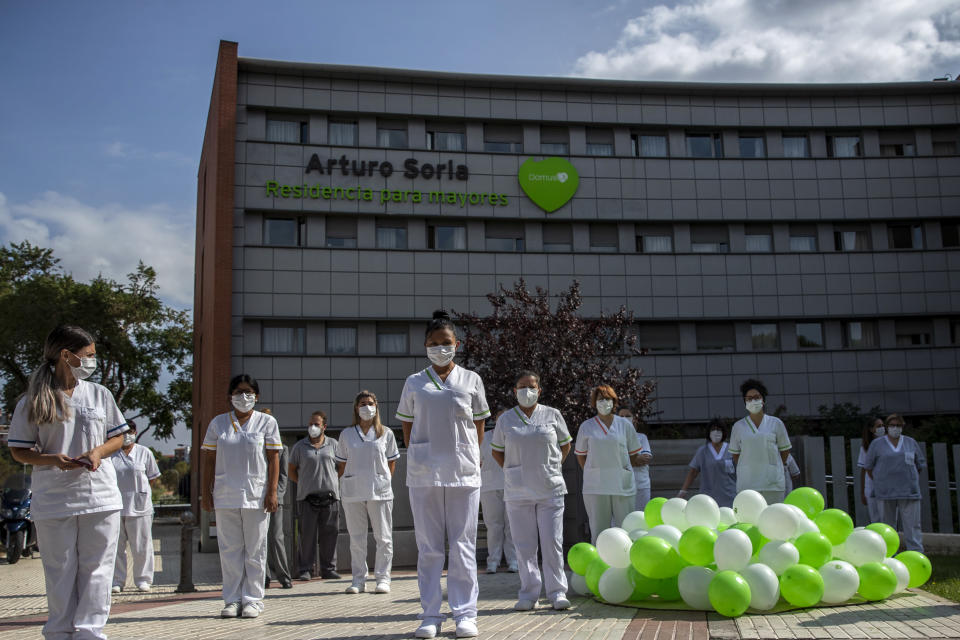 """Workers of a nursing home """"DomusVi Arturo Soria"""" hold a minute of silence in support of the social and health sector and its workers in Madrid, Spain, Tuesday, Sept. 15, 2020. After ending a strict lockdown in June having brought under control the virus transmission, Spain is now the European country where a second wave of the contagion is being more noticed. (AP Photo/Manu Fernandez)"""