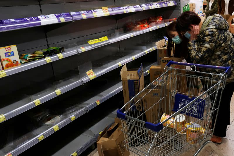 FILE PHOTO: Customers wear masks as they shop for instant noodles at a supermarket following the outbreak of a new coronavirus, in Hong Kong