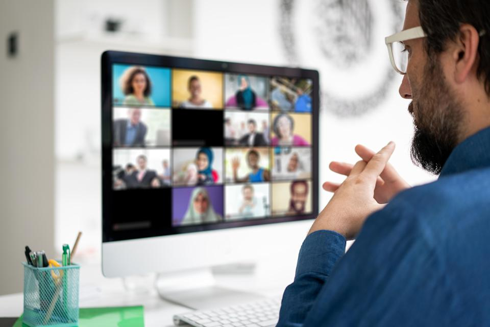 Image of a manager talking to his team via a video conference.