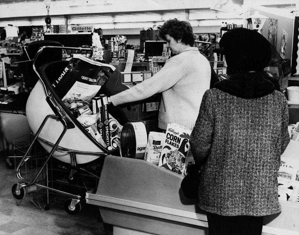 <p>A cashier unloads a very futuristic-looking shopping cart at checkout.</p>