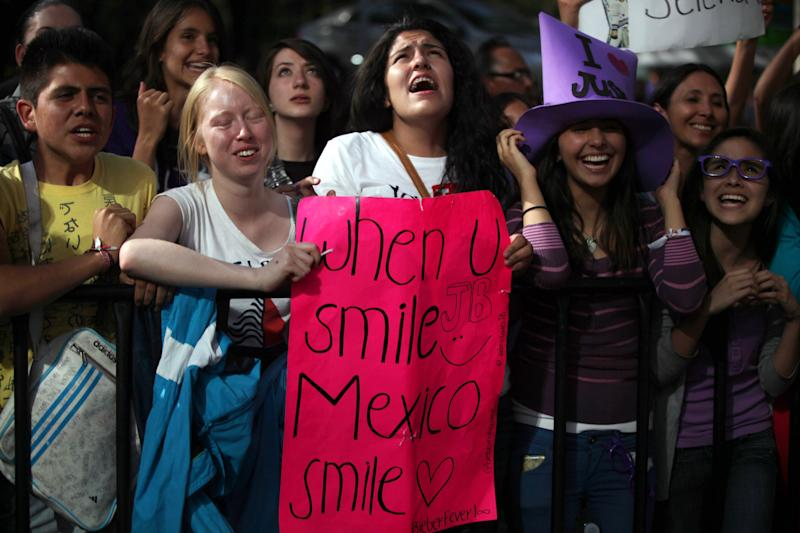 Fans of pop star Justin Bieber cheer outside a hotel where Bieber gave a news conference in Mexico City, Monday, June 11, 2012. Bieber will perform in a free open-air concert tonight at the Mexico City's main historic plaza, the Zocalo. (AP Photo/Alexandre Meneghini)