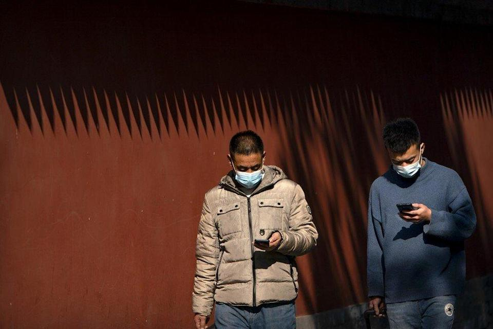People wearing face masks to protect against the spread of the coronavirus use their smartphones as they walk through Ditan Park in Beijing. Photo: AP