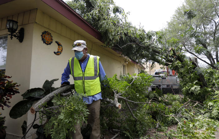 Juan Martinez helps clear debris left by Hurricane Hanna, Monday, July 27, 2020, in Weslaco,Texas. The area was flooded by Hurricane Hanna as it passed through the area dropping heavy rains which caused flooding. (AP Photo/Eric Gay)